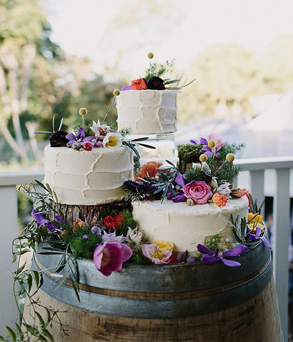 Three Separate Wedding Cakes Decorated With Spring Flowers Sitting On Barrel